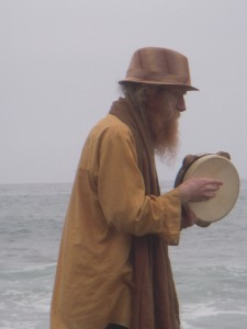David Alderdice playing the frame drume while walking on the beach.